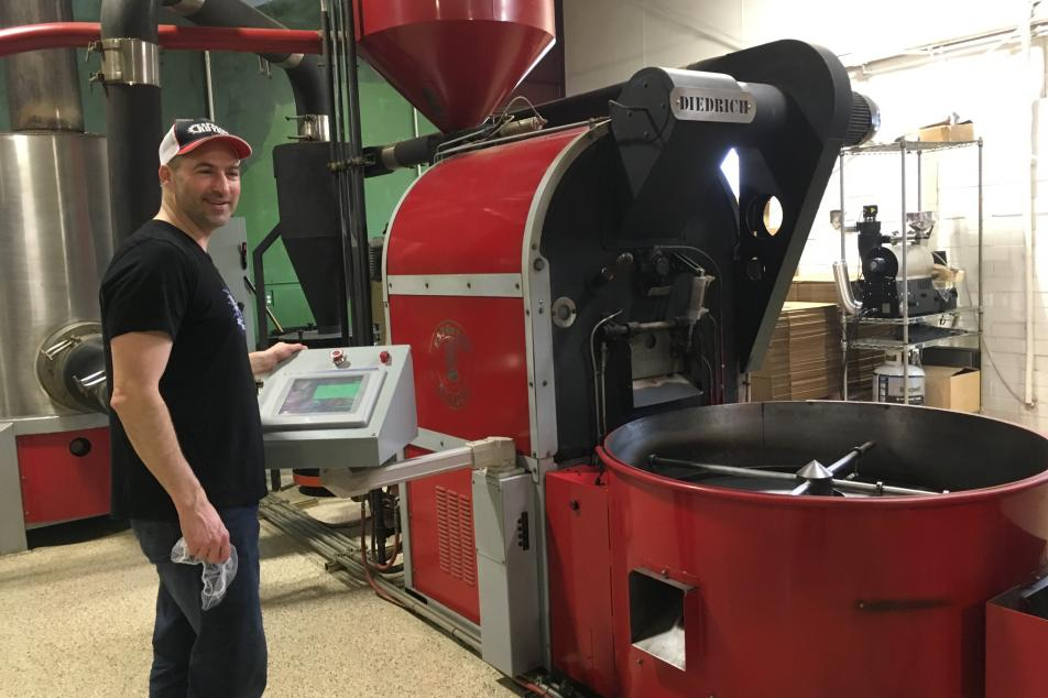 Male roaster with cap next to red coffee roaster