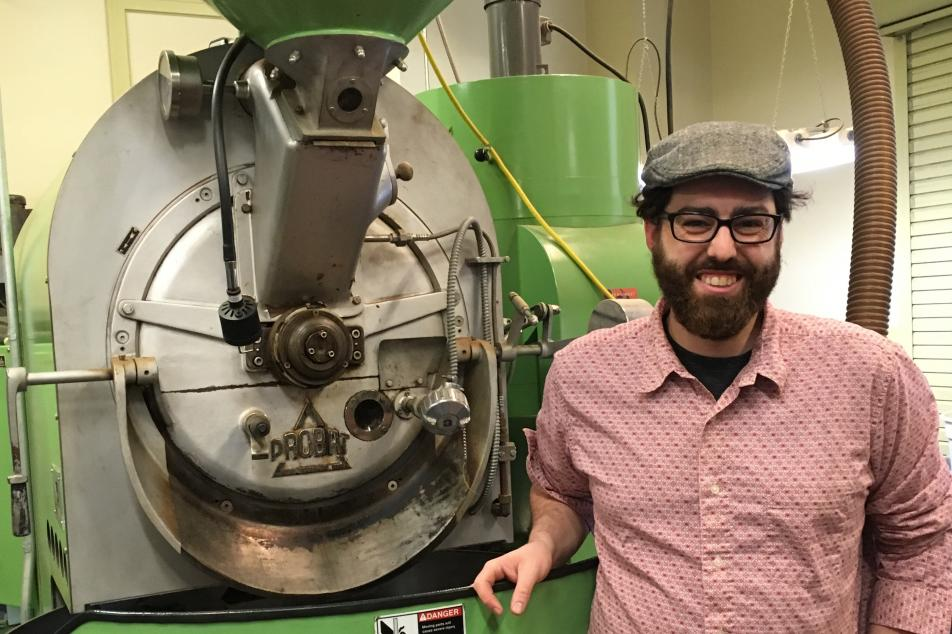 Green roaster and male with hat and beard next to it