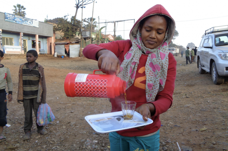 Female farmer pouring cup of Ethiopian coffee